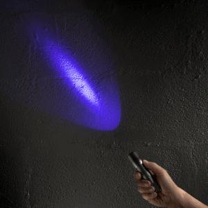main avec une lampe UV