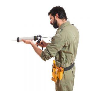 homme utilisant une pistolet à silicone