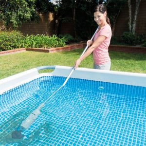femme en utilisant un balai de piscine