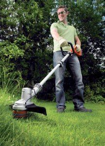 homme avec une débroussailleuse électrique dans le jardin