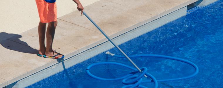 homme en utilisant un balai de piscine