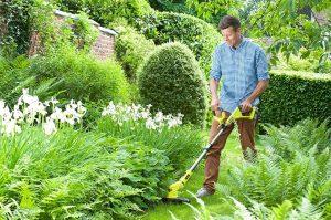 homme avec une débroussailleuse thermique dans le jardin